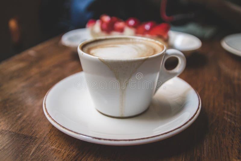 Taza blanca de café del latte con la torta imagen de archivo