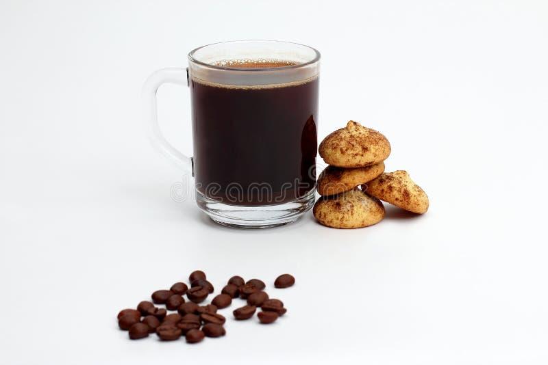 Taza blanca de café sólo con las galletas y las habas en el backg blanco fotos de archivo