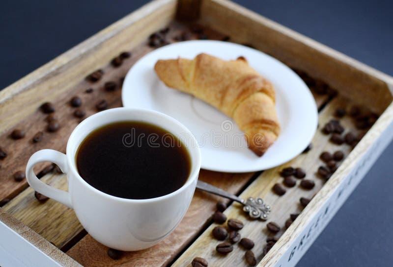 Taza blanca de café y de cruasán en la bandeja de madera imagen de archivo