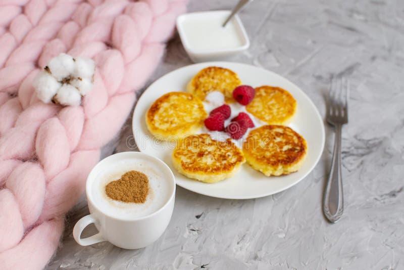 Taza blanca de capuchino del café con el modelo del corazón del canela, crepes del requesón con las frambuesas imagenes de archivo