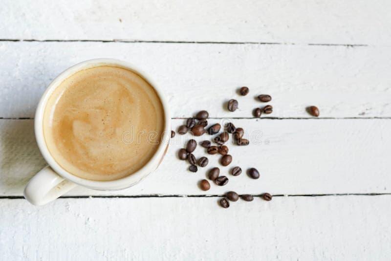 Taza blanca de coffe negro con las habas del coffe y copiar el espacio en el fondo de madera blanco fotografía de archivo libre de regalías