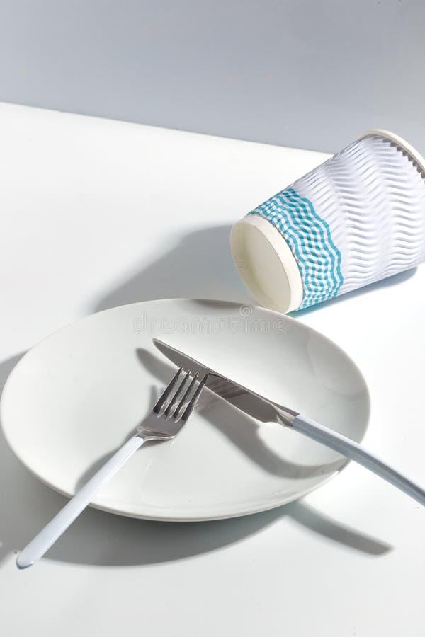 Taza blanca de la placa, de los cubiertos y de papel en una tabla brillante Concepto minimalistic de Cretive fotos de archivo