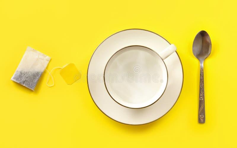 Taza blanca de la porcelana llenada de la agua caliente, de la bolsita de té y de la cuchara al lado de ella en el tablero amaril foto de archivo