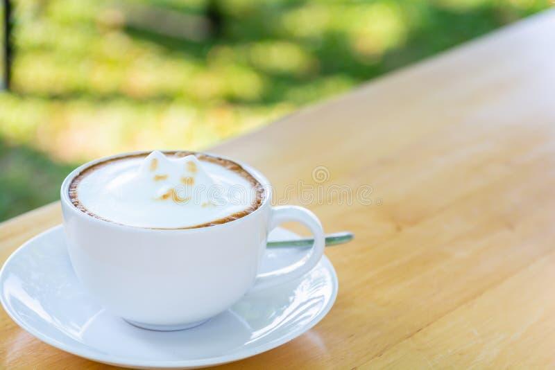Taza blanca de latte del café con espuma linda de la leche del arte del latte de la forma del gato en la tabla de madera imagenes de archivo