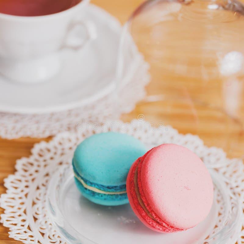 Taza blanca de té caliente, de macarrones y de galletas de torta dulce frescas Gusto de la menta y de la fresa En una servilleta  imágenes de archivo libres de regalías