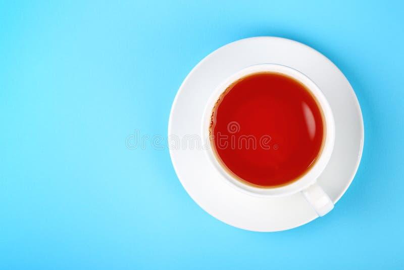 Taza blanca de té negro o rojo de la fruta sobre azul fotografía de archivo