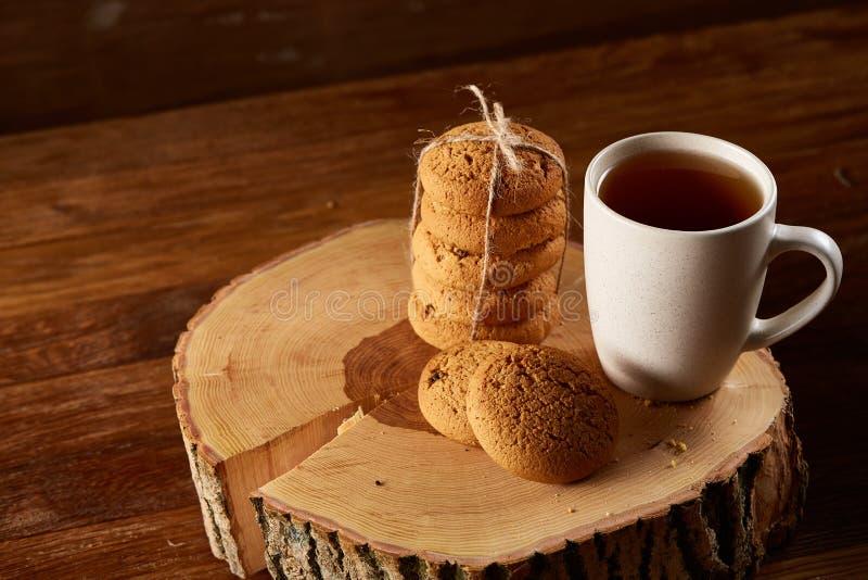 Taza blanca de té y manojo de galletas en un registro sobre el fondo de madera del estilo rural, primer, foco selectivo foto de archivo