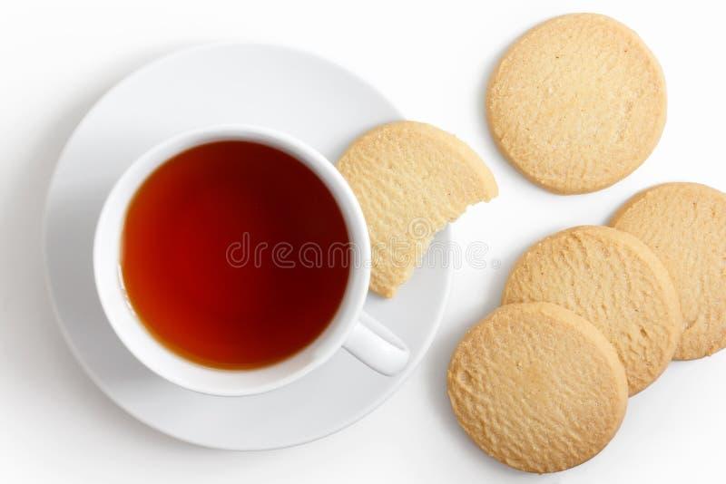 Taza blanca de té y platillo con las galletas de la torta dulce desde arriba imágenes de archivo libres de regalías