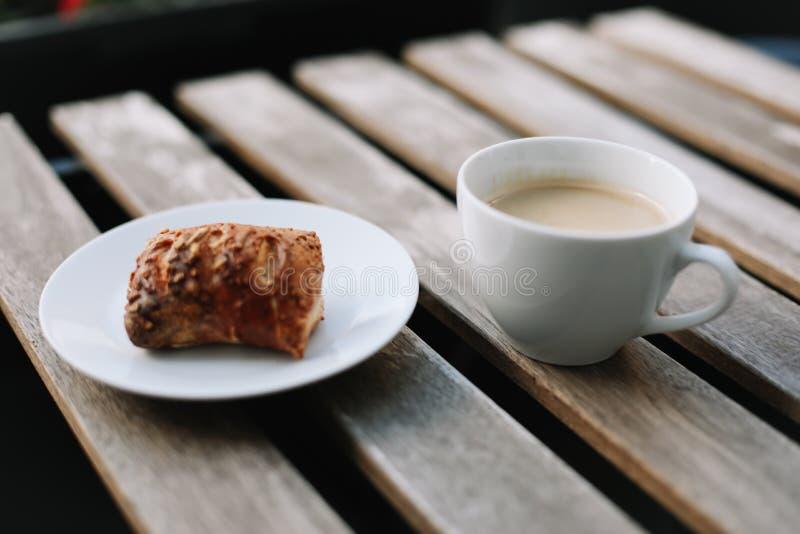 Taza blanca del café, cruasanes en fondo de madera de la tabla Concepto del desayuno Bollos y café o capuchino recientemente coci foto de archivo libre de regalías