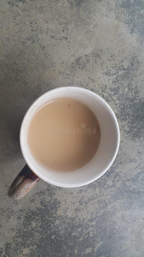 Taza blanca del café hermoso con leche-té negro sobre piso fotos de archivo libres de regalías