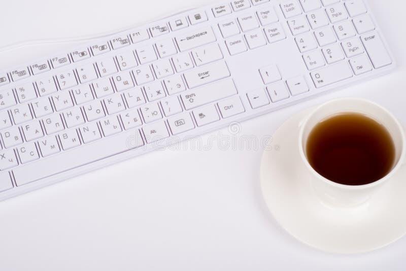 Taza blanca del teclado y de café, visión superior imagen de archivo