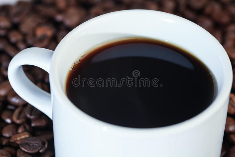 Taza blanca en granos de café foto de archivo