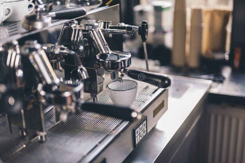 Taza blanca en la bandeja del goteo en máquina de café express foto de archivo