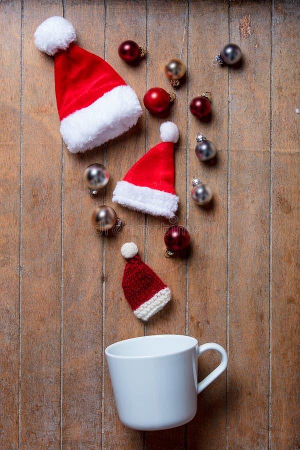 Taza blanca en la mentira en lado con el sombrero y las chucherías de Santa Claus fotos de archivo libres de regalías