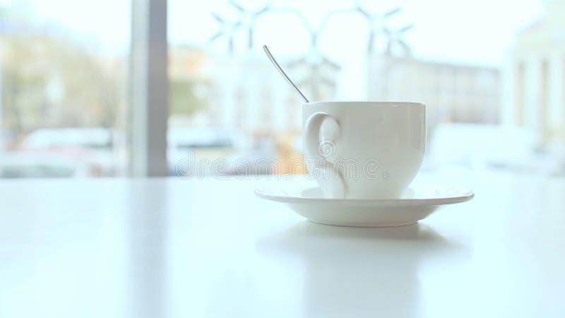 Taza blanca en la tabla en café contra una ventana del fondo imágenes de archivo libres de regalías