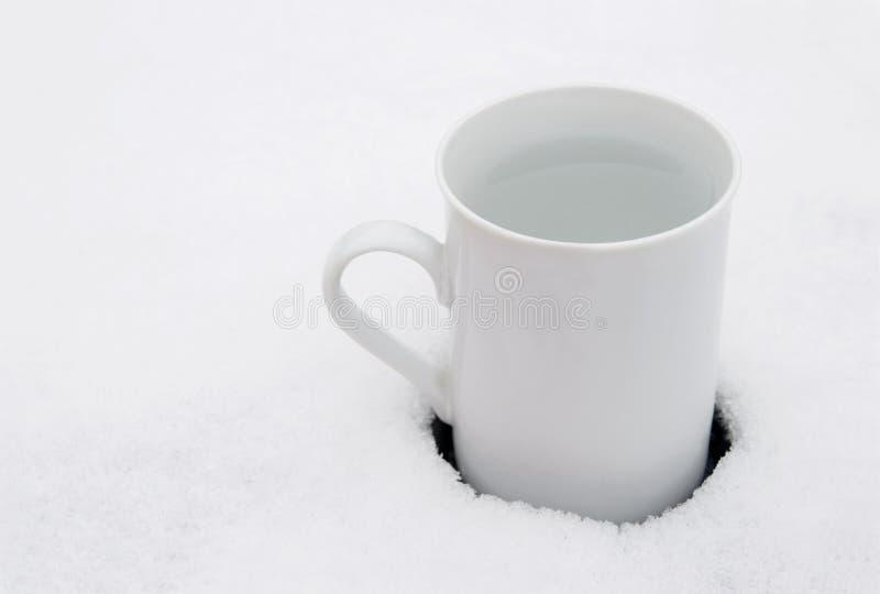 Taza blanca en nieve imagen de archivo