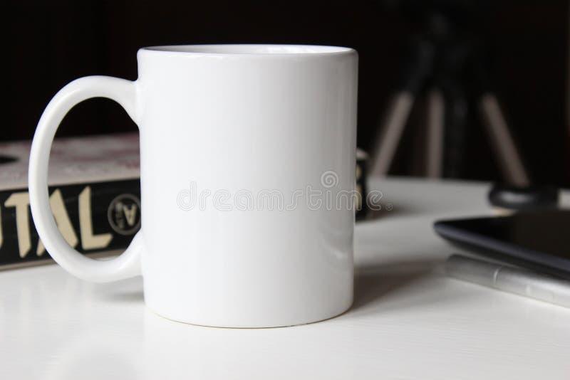 Taza blanca en una tabla fotos de archivo