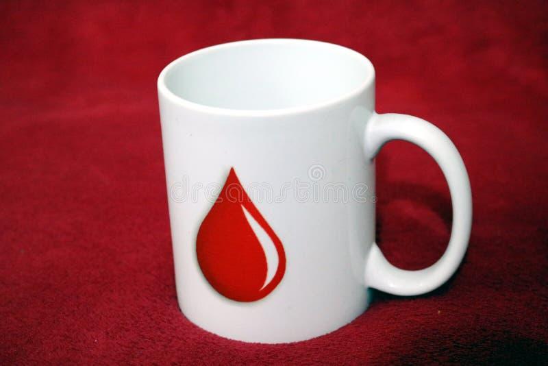 Taza blanca que tiene marca de la gota de sangre que inspira para donar sangre imagen de archivo libre de regalías
