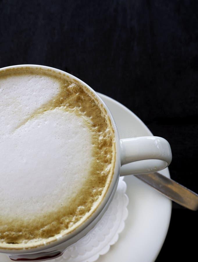 Taza blanca sabrosa de capuchino con arte del latte en la tabla de madera foto de archivo libre de regalías