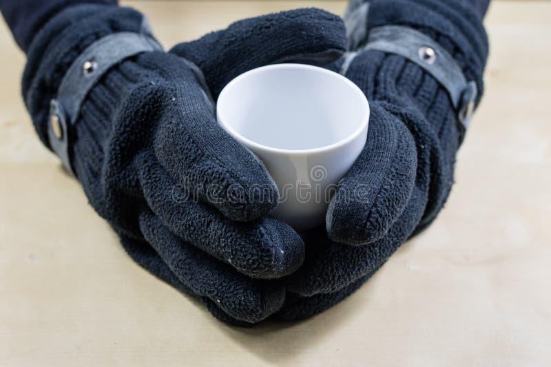 Taza blanca vacía con los guantes Manos en los guantes calientes que sostienen una barbilla imagen de archivo libre de regalías