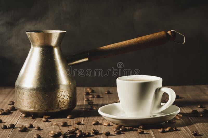 taza blanca y la cafetera con vapor caliente en un backgro de madera imagenes de archivo