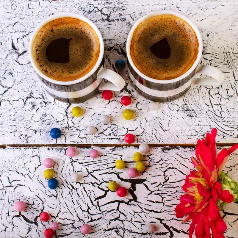 Taza blanco y negro con café, el caramelo y las flores en una luz wo fotos de archivo libres de regalías