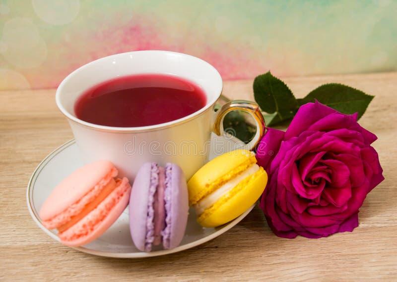 Taza caliente de té, de tortas coloreadas y de flor rosada imagen de archivo libre de regalías