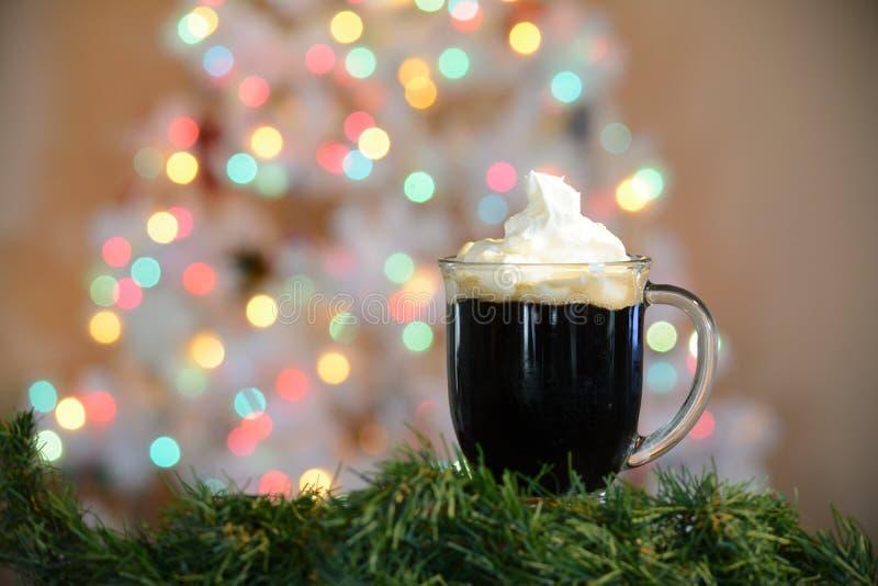 Taza caliente del cacao presentada delante del árbol de navidad blanco con las luces coloreadas imagen de archivo