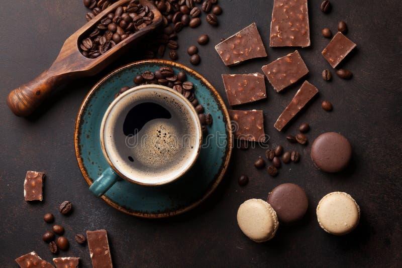 Taza, chocolate y macarrones de café en la tabla de cocina vieja fotografía de archivo
