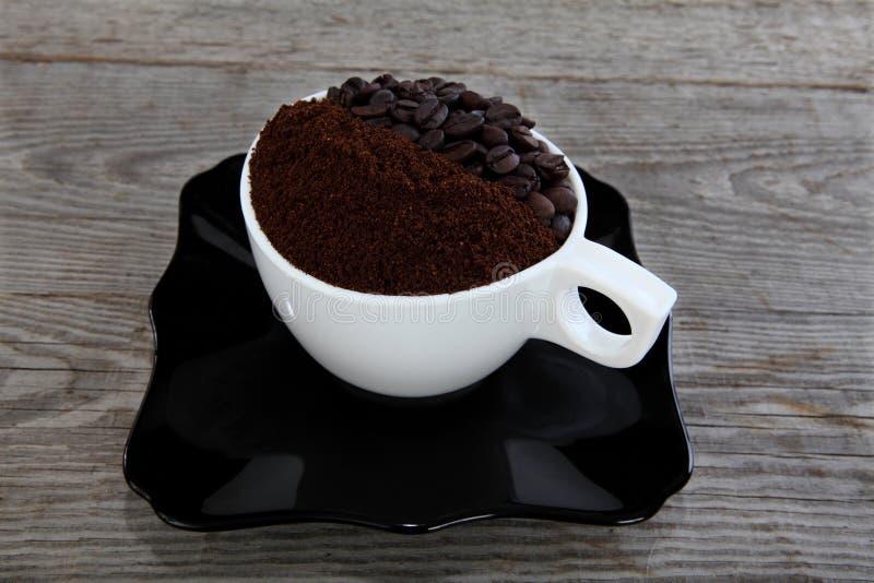 Taza con el café del grano de café y molido foto de archivo