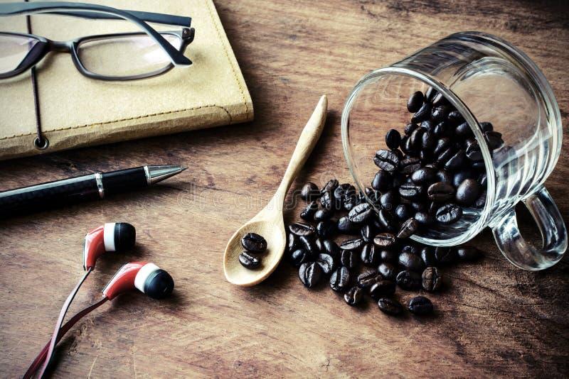 Taza con el grano y el cuaderno de café en la madera vieja imagen de archivo