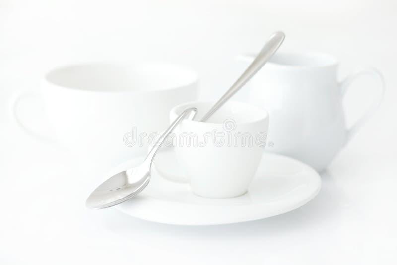 Taza con el platillo, el jarro de leche y la cuchara imagen de archivo