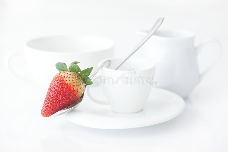 taza con el platillo, el jarro de leche y la fresa fotos de archivo libres de regalías