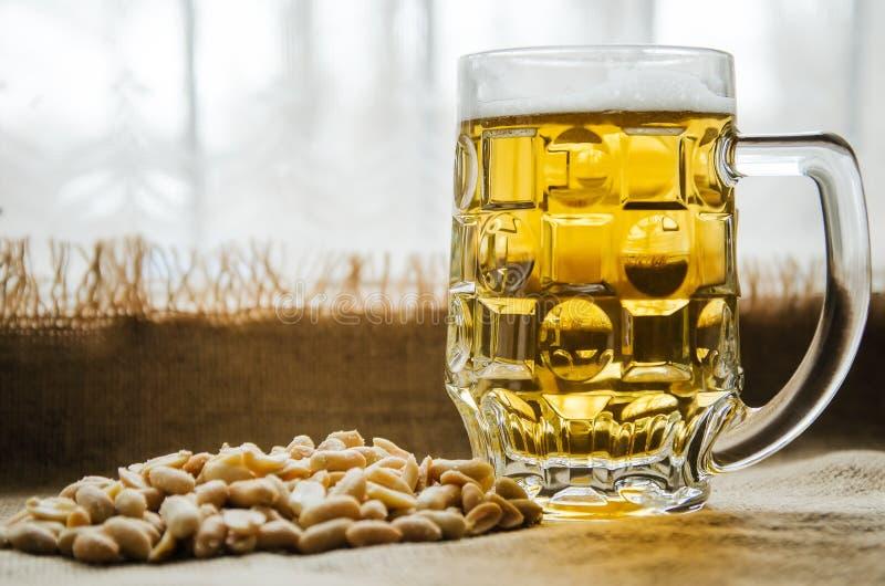 Taza con la cerveza y los cacahuetes salados en la tabla foto de archivo libre de regalías