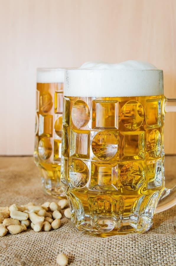 Taza con la cerveza y los cacahuetes salados en la tabla fotografía de archivo libre de regalías