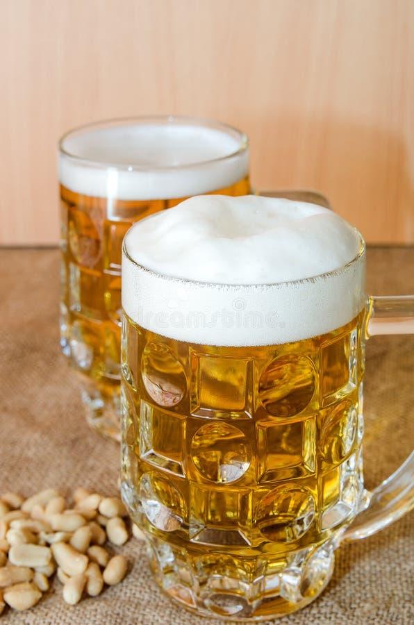 Taza con la cerveza y los cacahuetes salados en la tabla fotos de archivo