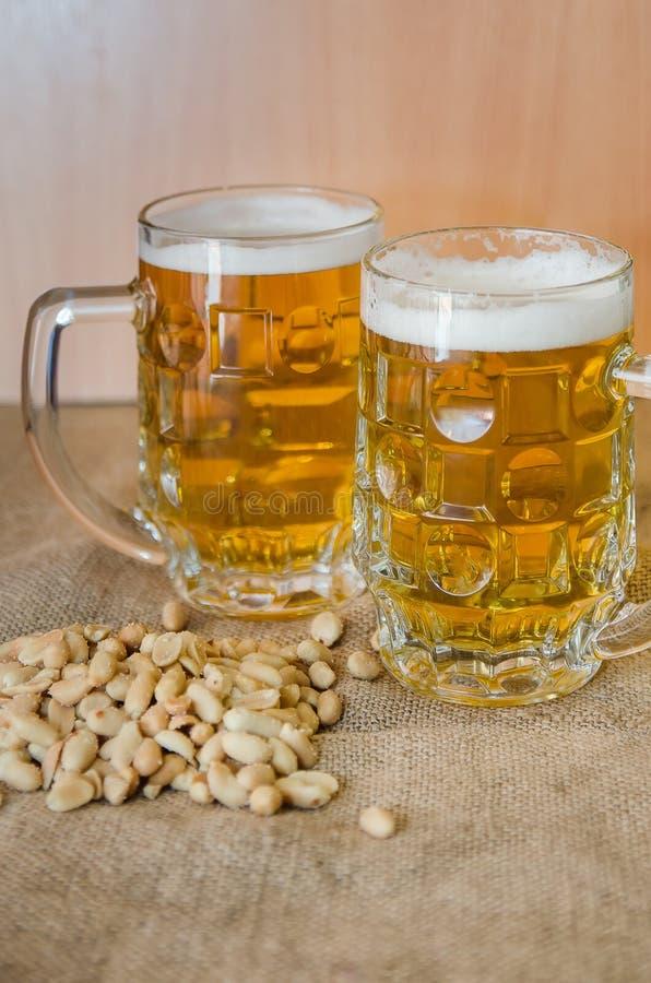 Taza con la cerveza y los cacahuetes salados en la tabla foto de archivo
