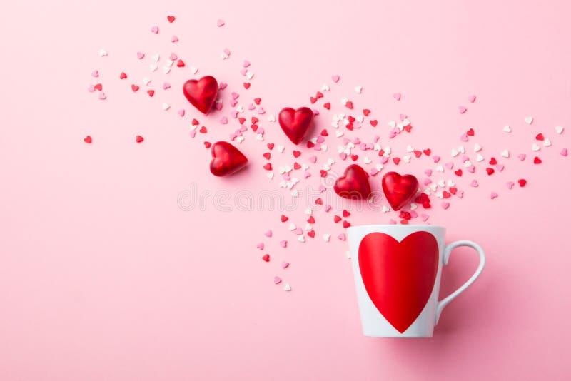 Taza con los corazones del azúcar y del chocolate en fondo rosado Composici?n plana de la endecha Rom?ntico, concepto del St d?a  fotos de archivo libres de regalías