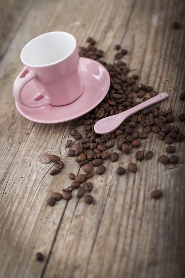 Taza con los granos de café en superficie de madera foto de archivo