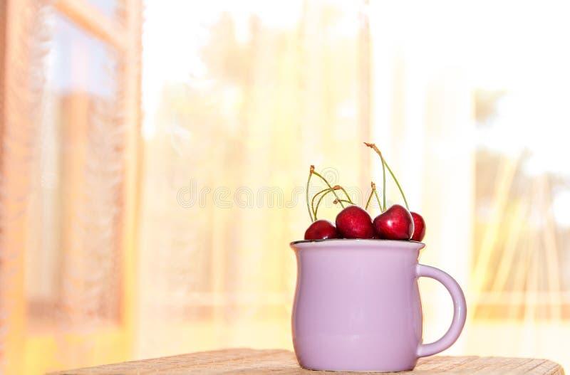 Taza con una cereza en un fondo de la ventana de la mañana fotografía de archivo libre de regalías