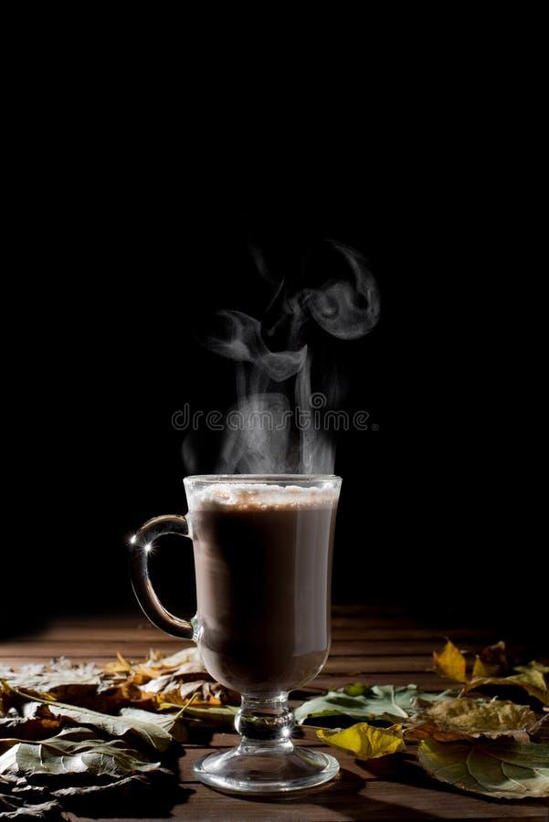 Taza de bebida caliente con vapor sobre fondo negro imagen de archivo libre de regalías
