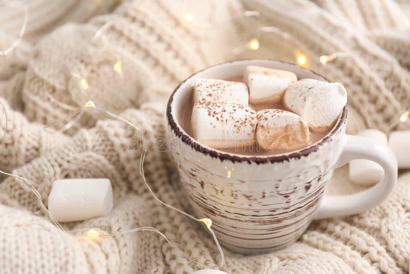 Taza de bebida caliente del cacao con las melcochas en la tela escocesa caliente fotos de archivo