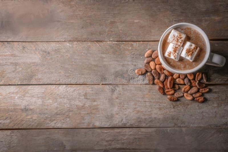 Taza de bebida deliciosa del cacao con las melcochas y las habas en la tabla de madera foto de archivo
