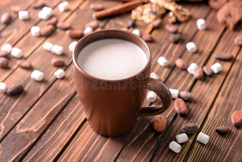Taza de bebida deliciosa del cacao con las melcochas y las habas en la tabla de madera foto de archivo libre de regalías