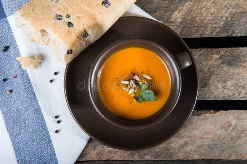 Taza de Brown con la sopa de la calabaza fotografía de archivo libre de regalías
