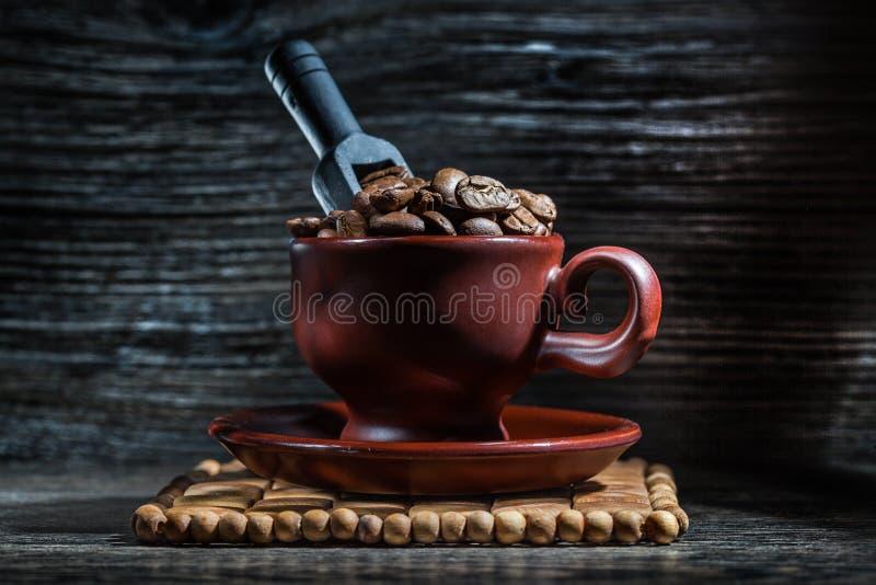 Taza de Brown con los granos de café y la pequeña cucharada negra fotos de archivo libres de regalías