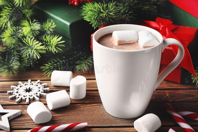 Taza de cacao caliente con las melcochas y las decoraciones de la Navidad en la tabla de madera foto de archivo