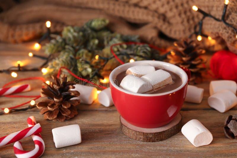Taza de cacao caliente con las melcochas y las decoraciones de la Navidad en la tabla de madera imagen de archivo libre de regalías