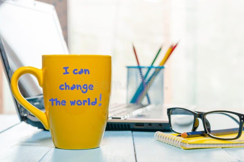 Taza de café amarilla de la mañana con el texto: Cambie el mundo Fondo de la oficina de negocios imagen de archivo libre de regalías