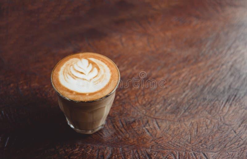 Taza de café ascendente cercana con arte del latte en la tabla de madera del grunge en el café fotos de archivo